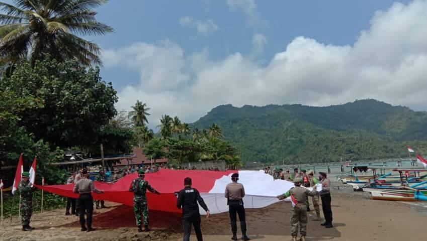 Polres Trenggalek melaksanakan apel pembentangan bendera Merah Putih raksasa sepanjang 76 meter di bibir Pantai Prigi Watulimo, Trenggalek, Senin (09/08/2021). (Foto: M. Zamzuri/Tugu Jatim)