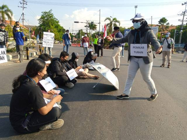"Warga Tuban menggelar aksi demo sebagai bentuk protes DPRD ""pelesiran"" ke Yogyakarta, di bundaran Patung Letda Sucipto dan di depan Gedung DPRD Tuban, Jumat (13/08/2021). (Foto: Mochamad Rochim/Tugu Jatim)"