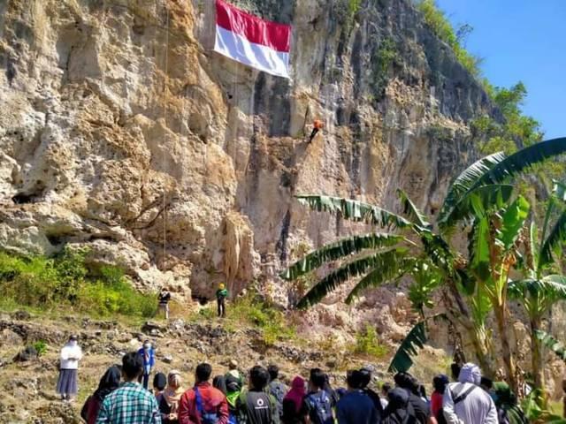 Anggota Mapala Guyub dan atlet panjat tebing di Tuban mengibarkan bendera Merah Putih di Puncak Tebing Sumur Pahit Semanding untuk memperingati HUT RI ke-76 pada Selasa (17/08/2021). (Foto: Mochamad Abdurrochim/Tugu Jatim)