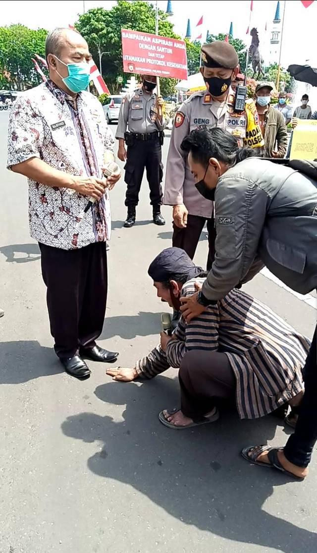 Salah satu seniman bernama Edy Ronggo memohon agar diberikan kelonggaran pentas dengan memegang kaki Kepala Disparbudpora Tuban Sulistiyadi di depan kantor Pemkab Tuban, Kamis (19/08/2021). (Foto: Mochamad Abdurrochim/Tugu Jatim)