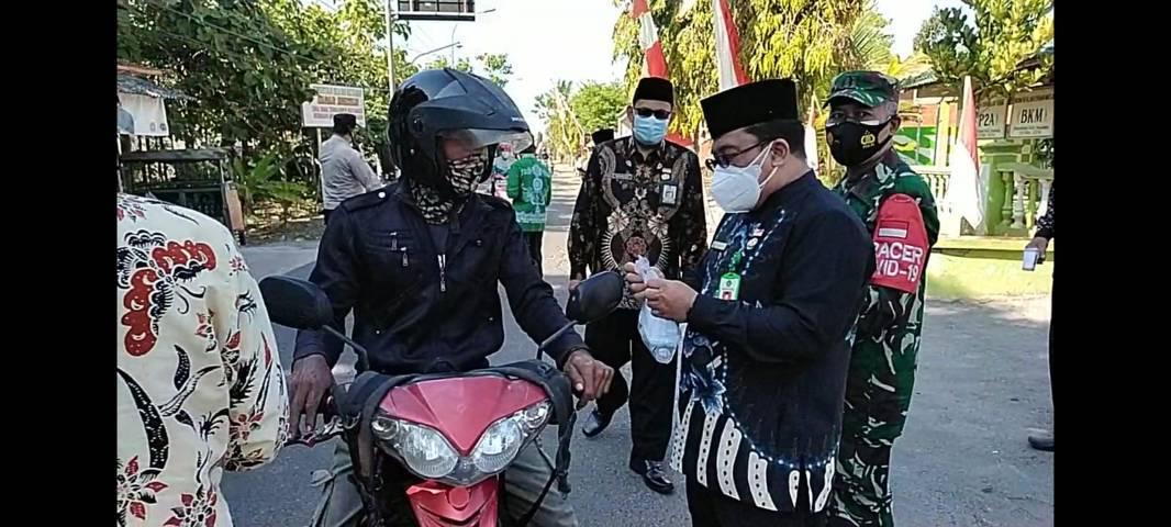 Sahid memberikan vitamin untuk pengendara motor di sekitar KUA Semanding, Kamis (12/08/2021). (Foto: Humas Kemenag Tuban/Tugu Jatim)