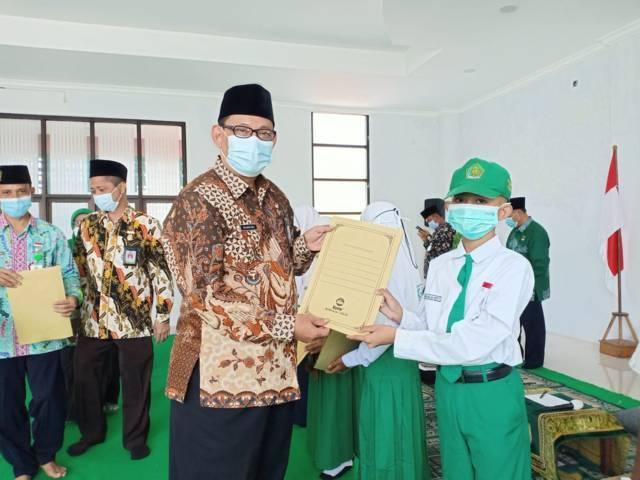Kasi Bimas Islam Kemenag Tuban Mashari menyerahkan santunan kepada anak yatim pada Jumat (20/08/2021). (Foto: Humas Kemenag Tuban/Tugu Jatim)