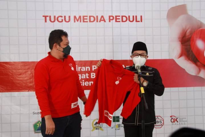 CEO Tugu Media Group Irham Thoriq memberikan kaus kepada Wali Kota Malang Sutiaji saat donor plasma konvalesen yang digagas Tugu Media Group di Aula Kantor DPRD Kota Malang pada Kamis (12/08/2021). (Foto: Rubianto/Tugu Jatim)