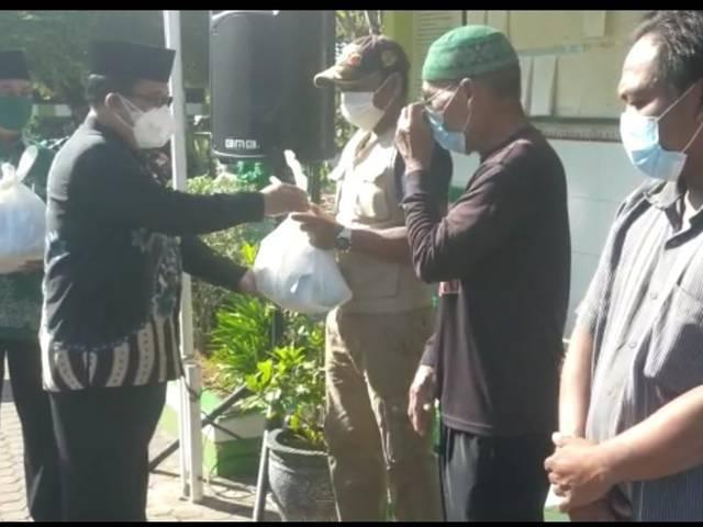 Kepala Kantor Kemenag Tuban Sahid menyerahkan paket sembako dan vitamin untuk warga terdampak Covid-19 di sekitar KUA Semanding, Kamis (12/08/2021). (Foto: Humas Kemenag Tuban/Tugu Jatim)