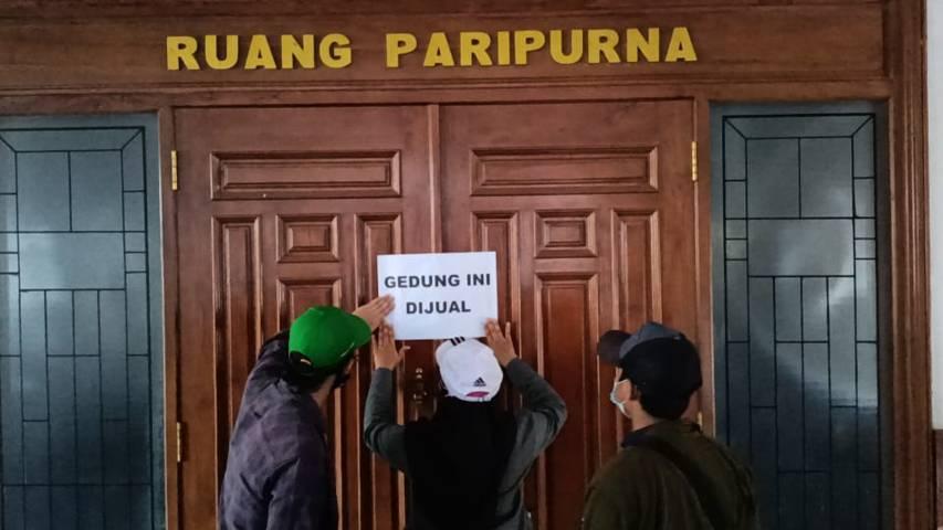 "Warga Tuban yang menggelar aksi demo menyegel ruang rapat paripurna yang berada di lantai dua dengan tulisan ""Ruangan Ini Dijual"" di Gedung DPRD Tuban, Jumat (13/08/2021). (Foto: Mochamad Rochim/Tugu Jatim)"