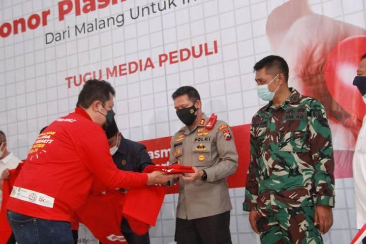 CEO Tugu Media Group Irham Thoriq memberikan kaus kepada Kapolresta Malang Kota AKBP Budi Hermanto saat donor plasma konvalesen yang digagas Tugu Media Group di Aula Kantor DPRD Kota Malang pada Kamis (12/08/2021). (Foto: Rubianto/Tugu Jatim)
