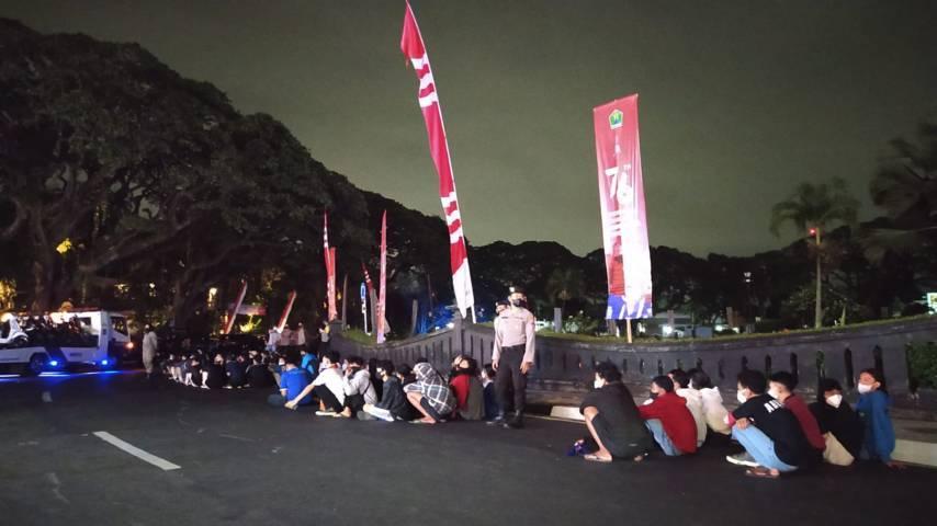 Puluhan Aremania diamankan petugas gabungan saat merayakan HUT Arema ke-34 di depan Alun-Alun Tugu Balai Kota Malang, Selasa malam (10/08/2021). (Foto: Azmy/Tugu Jatim)