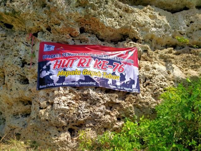 Banner anggota Mapala Guyub Tuban terpampang di Puncak Tebing Sumur Pahit Semanding Tuban saat memperingati HUT RI ke-76 pada Selasa (17/08/2021). (Foto: Mochamad Abdurrochim/Tugu Jatim)