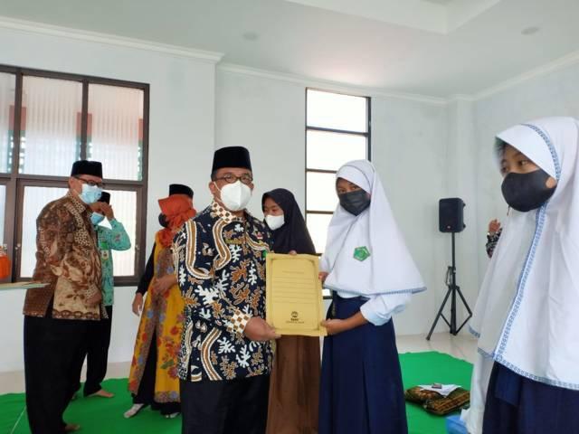 Kepala Kantor Kemenag Kabupaten Tuban Sahid menyerahkan santunan kepada anak yatim saat memperingati 1 Muharram pada Jumat (20/08/2021). (Foto: Humas Kemenag Tuban/Tugu Jatim)