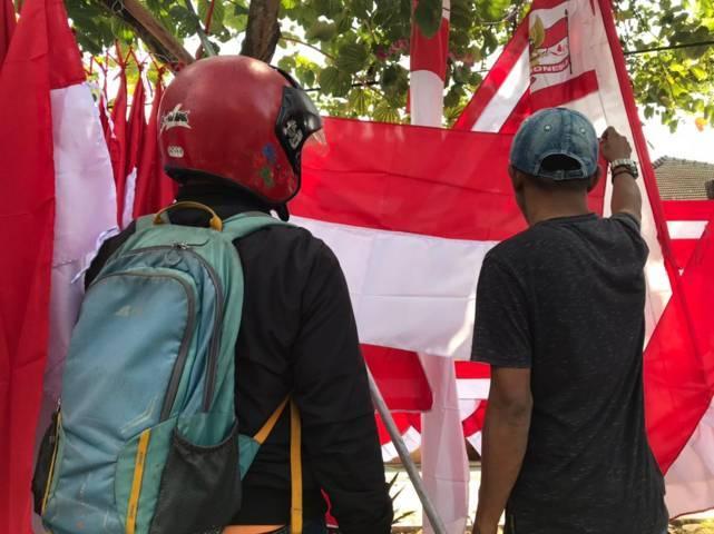 Salah seorang calon pembeli bendera menanyakan pada salah satu penjual bendera di Sawojajar, Kota Malang, Selasa (3/7/2021). (Foto: Rizal Adhi/Tugu Malang/Tugu Jatim)