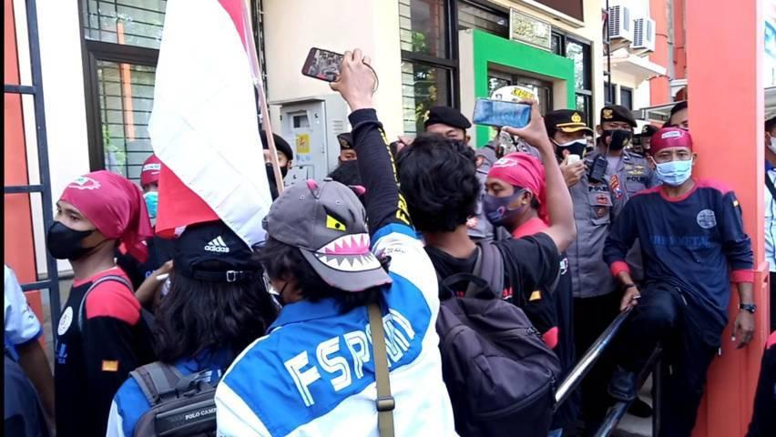 Ratusan massa buruh tampak memaksa masuk kantor Dinas PMPTSP Tuban, Selasa (3/8/2021). Mereka menuntut ada perbaikan kinerja dinas dalam mempedulikan serikat pekerja. (Foto: Moch Abdurrochim/Tugu Jatim)