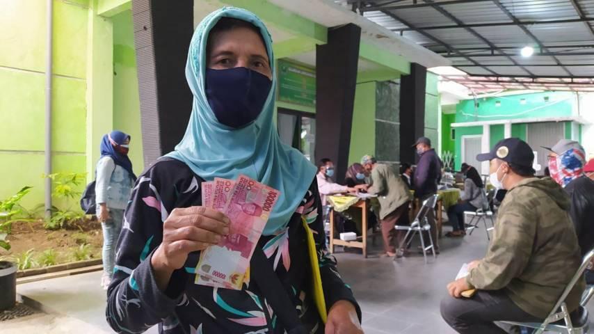 Salah satu warga yang menerima dana bansos di Kantor Kecamatan Lowokwaru, Kota Malang, Selasa (03/08/2021). (Foto:Azmy/Tugu Jatim)