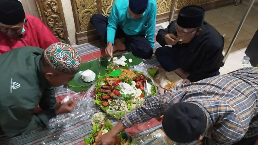 Warga memakan makanan setelah upacara tolak bala selesai dilakukan pada Kamis Legi (08/07/2021). (Foto:Azmy/Tugu Jatim)
