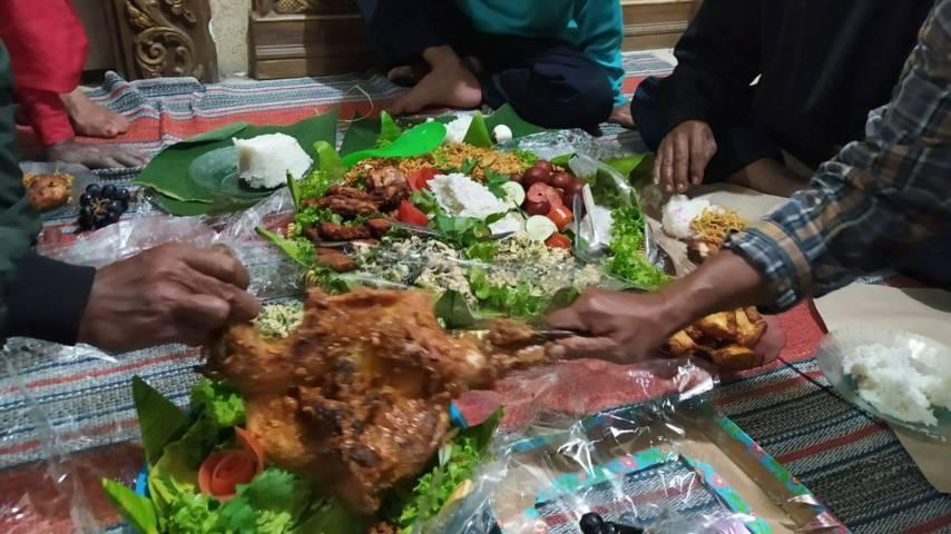 Nikmatnya makanan setelah upacara tolak bala pada Kamis Legi (08/07/2021). (Foto:Azmy/Tugu Jatim)