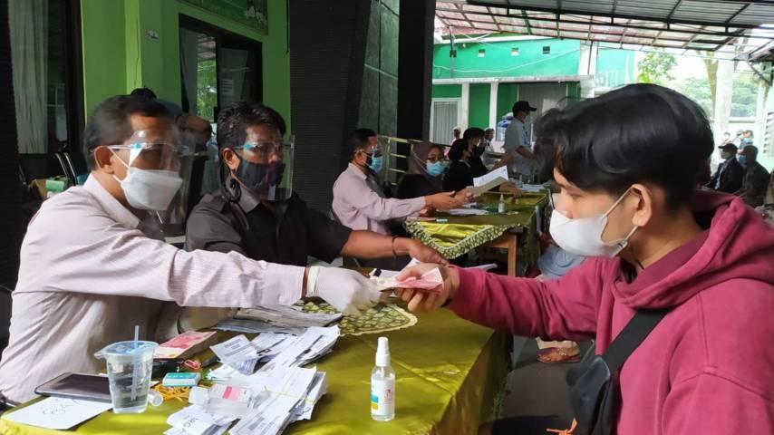 Salah satu petugas yang menyerahkan dana bansos kepada warga di Kantor Kecamatan Lowokwaru, Kota Malang, Selasa (03/08/2021). (Foto:Azmy/Tugu Jatim)