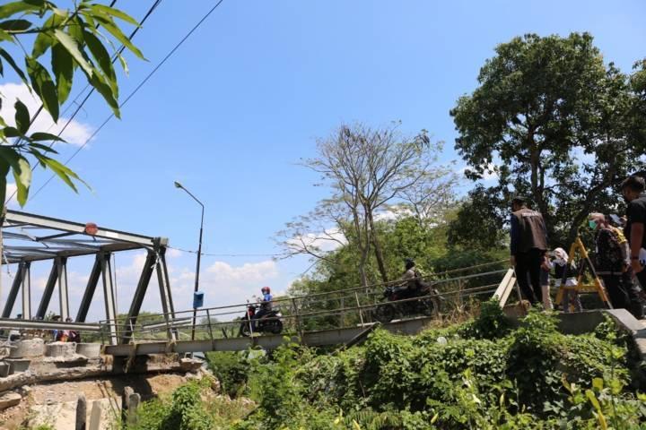Kondisi jembatan yang terputus aksesnya, akibat abrasi Sungai Bengawan Solo. Terlihat jembatan darurat yang berukuran kecil yang bisa dilewati pejalan kaki dan sepeda motor. (Foto: Humas Pemkab Tuban) tugu jatim