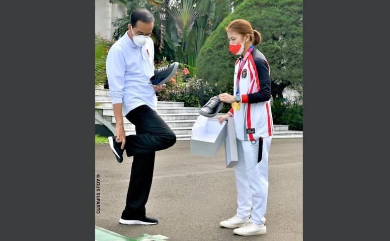 Presiden Jokowi kala mencoba sepatu sneaker baru buatan Greysia Polii di Istana Kepresiden Bogor, Jumat (13/8/2021). (Foto: Instagram/Jokowi) tugu jatim