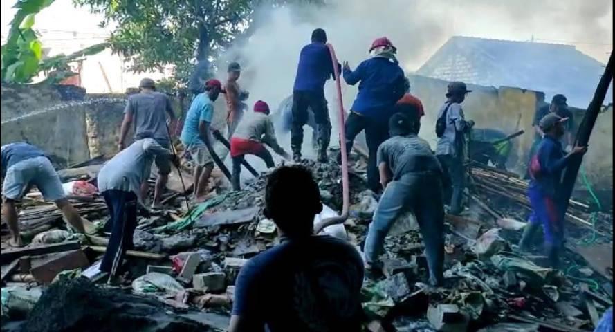 Petugas pemadam kebakaran dari BPBD Tuban bersama warga saat berada di tengah kepungan asap tebal akibat kebakaran kayu material proyek hotel di Tuban, Minggu (1/8/2021). (Foto: Humas BPDB Tuban) tugu jatim