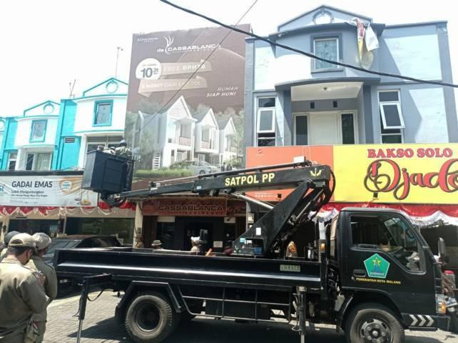 Operasi penindakan reklame menunggak pajak oleh Bapenda Kota Malang bersama Satpol PP Kota Malang, Kamis (19/8/2021). (Foto: Dokumen) tugu jatim