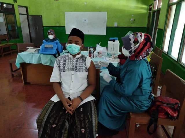 Proses vaksinasi yang digelar oleh Kodim 0811 Tuban dan dilakukan di Ponpes Sunan Bejagung Jumat (20/8/2021). (Foto: Dokumen/Penerangan Kodim 0811 Tuban) tugu jatim