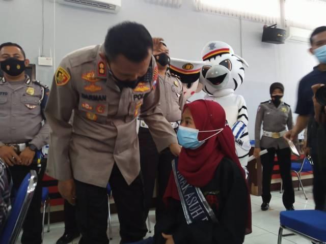 Kapolres Tuban AKBP Darman saat menyapa salah satu anak yatim yang diangkat sebagai anak asuh oleh jajaran anggota Satlantas Polres Tuban, Jumat (17/9/2021). (Foto: Moch Abdurrcohim/Tugu Jatim)