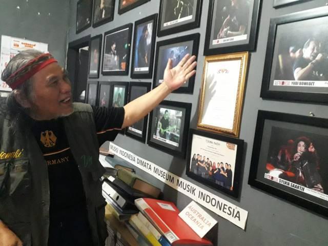 Hengki Herwanto, pendiri Museum Musik Indonesia saat menunjukkan dereta koleksi-koleksi musik dan foto-foto musisi zaman dulu. (Foto: M Sholeh/Tugu Malang/Tugu Jatim)