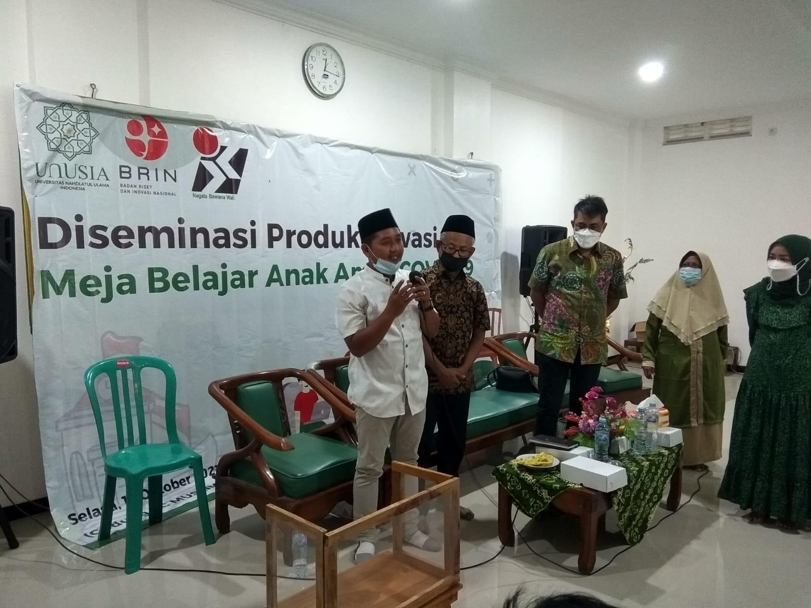 Direktur Yayasan Tanali Zakky Alayyubi memperlihatkan meja belajar aman Covid-19 ke sejumlah peserta penerima bantuan. (Foto: Dokumen/Tugu Jatim)