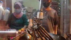 Dartadi dengan lengan kirinya yang patah memasak nasi goreng dengan mesin pengaduk hasil inovasinya serta dibantu istrinya pada Kamis malam (14/10/2021). (Foto: M. Sholeh/Tugu Malang/Tugu Jatim)