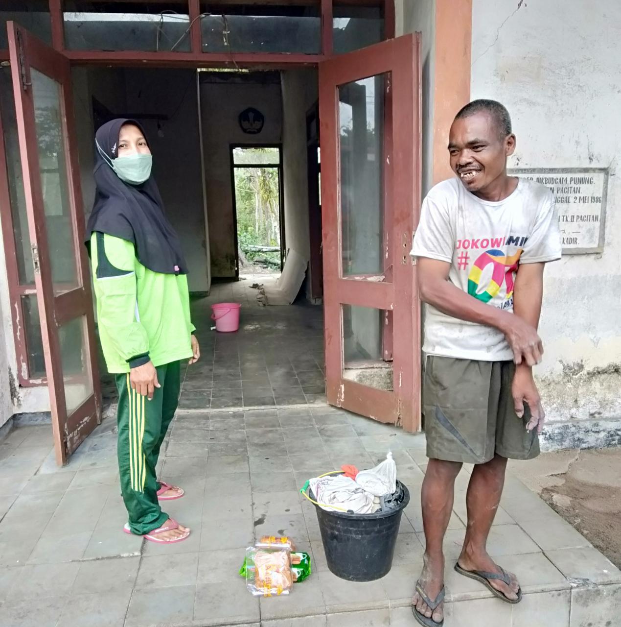 Murwati Handayani, relawan ODGJ, ketika menyambangi Bambang, ODGJ yang tinggal di gedung tua di depan SMAN Punung Kabupaten Pacitan. (Foto: Risma Wigati/Tugu Jatim)