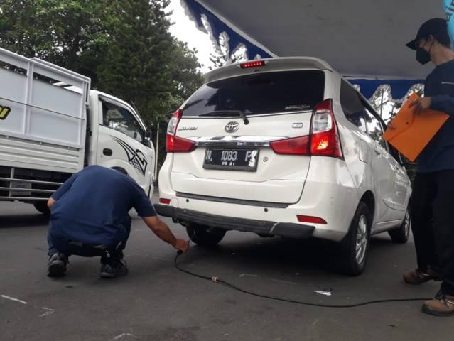 Petugas melakukan uji emisi kendaraan roda 4 di Jalan Simpang Balapan Kota Malang, Selasa (5/10/2021). (Foto: M Sholeh/Tugu Malang/Tugu Jatim)